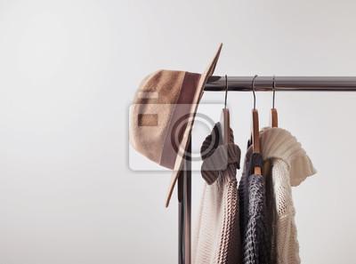 Fototapeta Dziane swetry na wieszakach i filcowym kapeluszu
