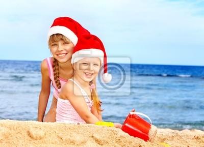 Dzieci w santa hat gry na plaży.
