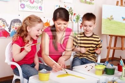 Dzieci z nauczycielem narysować farby w pokoju gry .