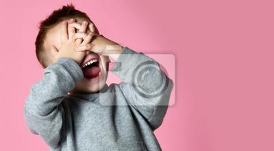 Fototapeta Dziecko chłopca obejmujące zamknięcie oczu rękami i dłońmi krzyczącymi, śmiejąc się z różu