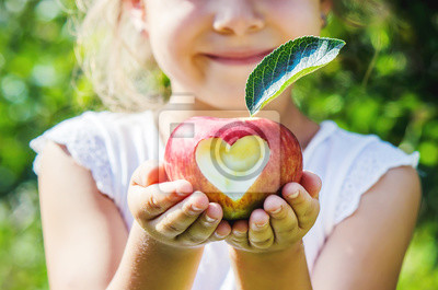 Fototapeta Dziecko z jabłkiem. Selektywne skupienie. Ogród.