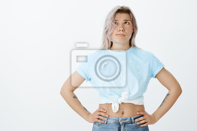 Dziewczyna jest zmęczona sprzątaniem przez cały dzień. Portret wyczerpanej pięknej koleżanki w stylowym oufit, trzymając się za ręce na biodrach, patrząc w górę podczas dmuchania kosmykiem włosów z tw