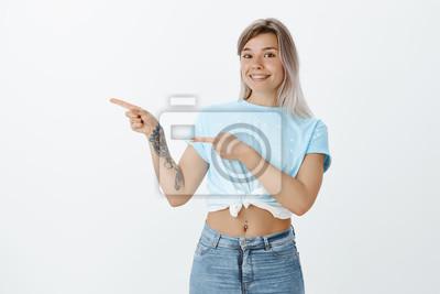 dziewczyna nie może trzymać szczęścia widząc sławną osobę. Podekscytowany radosny europejski kobieta z jasnymi włosami i tatooed ramię, wskazując w lewo z palcami wskazującymi i szeroko uśmiechając si