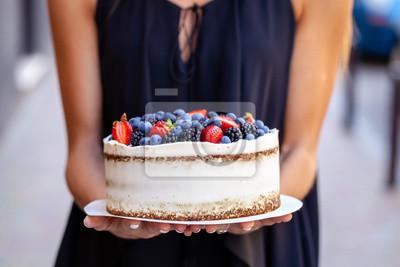 Fototapeta Dziewczyna trzyma tort z leśnymi jagodami, truskawkami, jagodami, na ulicy w mieście. Koncepcja produkcji ciast, piekarni, restauracji. Zdjęcie w tle
