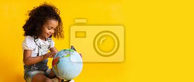 Fototapeta Early education. Little girl pointing to world globe