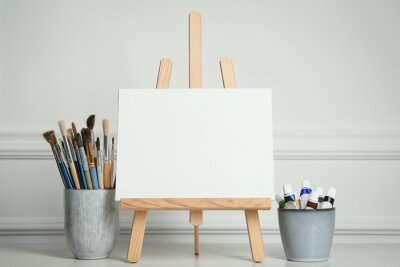 Fototapeta Easel with blank canvas, paints and brushes on white wooden table
