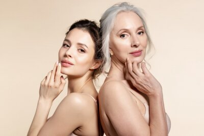 Fototapeta Elderly and young women with smooth skin and natural makeup standing back-to-back.
