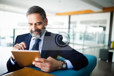 Fototapeta Elegant business multitasking multimedia man using devices