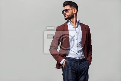 Fototapeta Elegant young handsome man in suite wearing glasses. Studio fashion portrait.