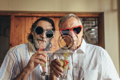 Fototapeta Emerytowani mężczyźni noszący śmieszne okulary do picia sok