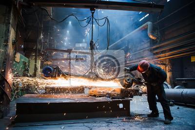 Fototapeta Employee grinding steel with sparks - focus on grinder. Steel factory.