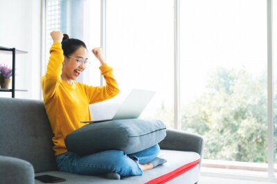 Fototapeta Excited female feeling euphoric celebrating online win success achievement result, young asian woman happy about good email news, motivated by great offer or new opportunity