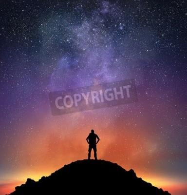 Fototapeta Excursionist na górze obserwować jasne niebo pełne gwiazd