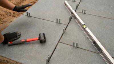 Fototapeta Expert workman laying patio slabs in garden makeover