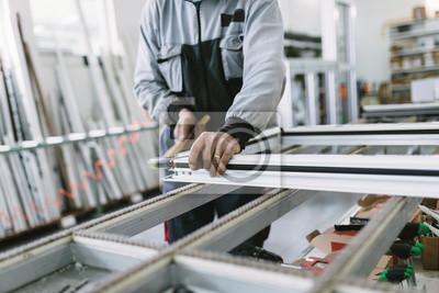 Fototapeta Fabryka do produkcji okien i drzwi aluminiowych i PVC. Ręczna robota montażowa drzwi i okien PCV. Selektywne fokus.