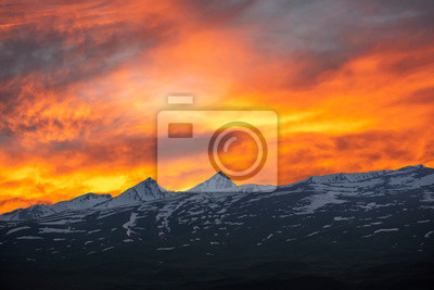 Fairy sunset. Beautiful orange sky with colorful clouds over the mountains. Armenia Aragats mountains.