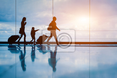 Fototapeta Family at airport travelling with young child and luggage walking to departure gate, girl pointing at airplanes through window, silhouette of people, abstract international air travel concept