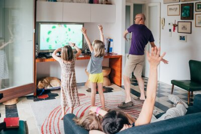 Fototapeta Family dancing together indoor playing videogame