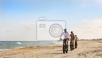 Fototapeta Family rides their e bikes on the beach in the Baja.