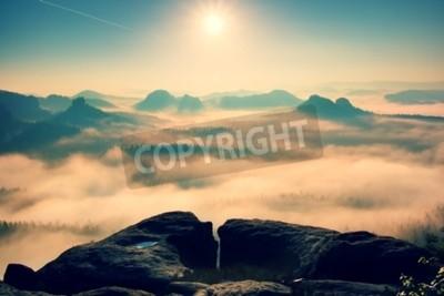 Fototapeta Fantastyczna rozmarzona wschód słońca na szczycie skalistej góry z widokiem na dolinę w mglisty