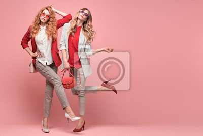 Fototapeta Fashionable woman with stylish hairstyle, makeup dance. Two Shapely blonde redhead girl having fun, trendy red outfit, heels, fashion hair, make up. Excited model, beauty dancing fun concept on pink