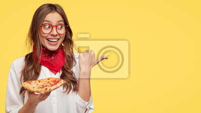 Fototapeta Fastfood i posiłek koncepcja. Wesoła młoda dziewczyna uśmiecha się przyjemnie, zjada smaczny kawałek pizzy, będąc w dobrym nastroju, pokazuje miejsce, które kupiła, reklamuje pizzerię, izolowaną na żó