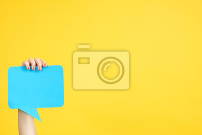 Fototapeta Feedback concept. Hand holding blue speech bubble. Copy space on yellow background.