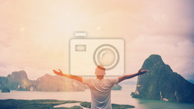 Fototapeta Feel good freedom and travel adventure concept. Copy space of happy man raise hands on  top of mountain with sun light abstract background.