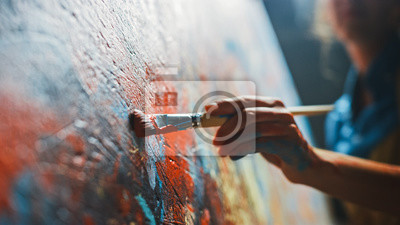 Fototapeta Female Artist Works on Abstract Oil Painting, Moving Paint Brush Energetically She Creates Modern Masterpiece. Dark Creative Studio where Large Canvas Stands on Easel Illuminated. Low Angle Close-up