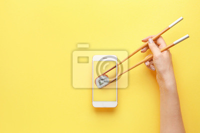 Fototapeta Female hand holding chopsticks and mobile phone with tasty sushi roll on screen against color background