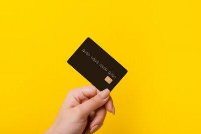 Fototapeta Female hand holding credit card on yellow background