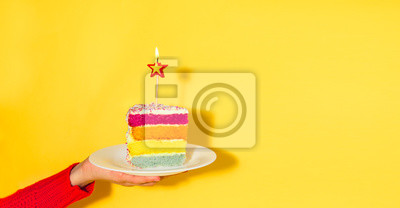Fototapeta Female hand holding white plate with slice of Rainbow cake with birning candle in the shape of star isolated on yellow background. Happy bithday, party concept. Wide banner. Copy space.