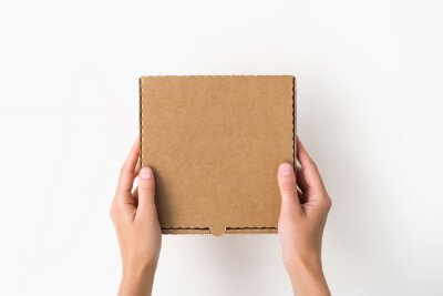 Fototapeta female hands holding a small cardboard box on a white background. packaging and delivery concept, top view