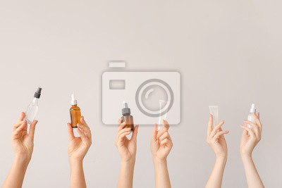 Fototapeta Female hands with different cosmetic products in bottles on grey background