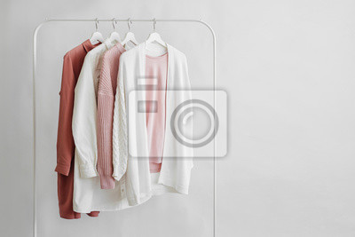 Fototapeta Feminine clothes in pastel pink  color on hanger on white background.  Elegant dress,  jumper, shirt and other fashion outfit. Spring cleaning home wardrobe. Minimal concept.