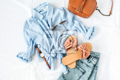Fototapeta Feminine summer fashion composition with blouse, slippers, purse, sunglasses, watch, jean shorts on white background. Flat lay, top view minimalist clothes collage. Female fashion blog, social media.