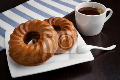 filiżanka kawy, okrągłe ciasto na ciemnym stole