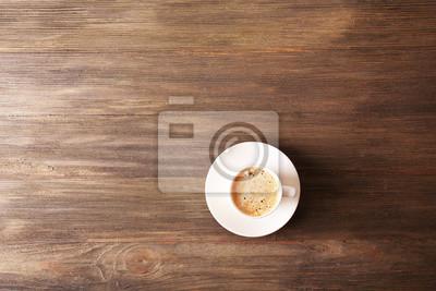 Filiżanka kawy z pianką na drewnianym stole, widok z góry