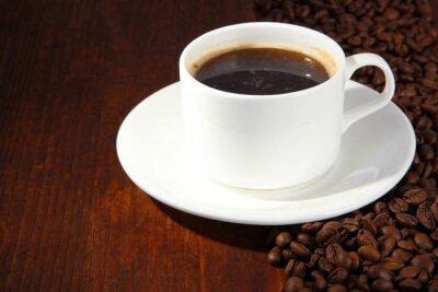 Filiżanka kawy z ziaren kawy na tle drewniane
