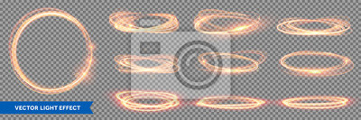 Fototapeta Fire light circles trails of sparkling gold glitter, vector glow flare swirls on transparent background. Abstract vector fire circles, sparkling swirls and energy light spiral frames