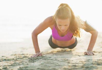 Fototapeta Fitness młoda kobieta robi push up na plaży
