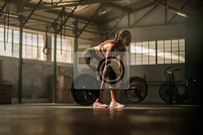 Fototapeta Fitness model performing weight lifting exercise at gym