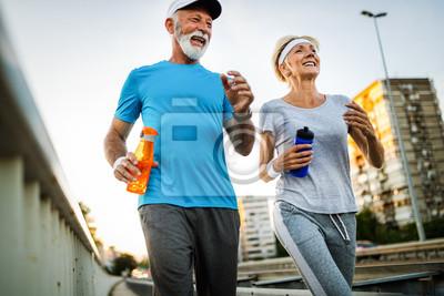 Fototapeta Fitness, sport, people, exercising and lifestyle concept - senior couple running