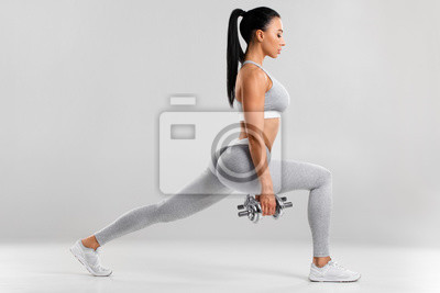 Fototapeta Fitness woman doing lunges exercises for leg muscle workout training. Active girl doing front forward one leg step lunge exercise, on the gray background