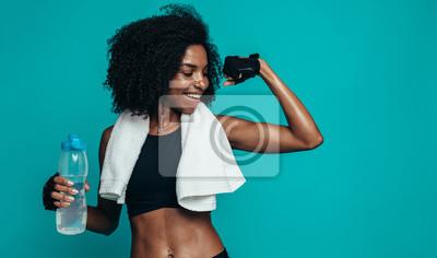 Fototapeta Fitness woman flexing muscles