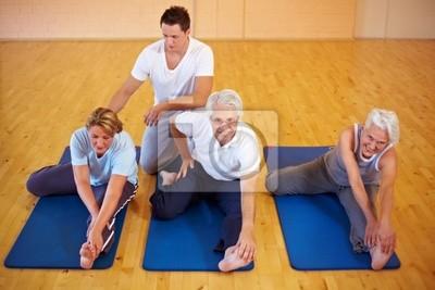 Fitnesstrainer zeigt Dehnübungen