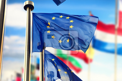 Fototapeta Flagi UE falujące na błękitnym niebie. Bruksela, Belgia