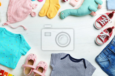 Fototapeta Flat lay composition with cute clothes and space for text on white wooden background. Baby accessories