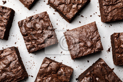 Fototapeta Flat lay composition with fresh brownies on parchment paper. Delicious chocolate pie