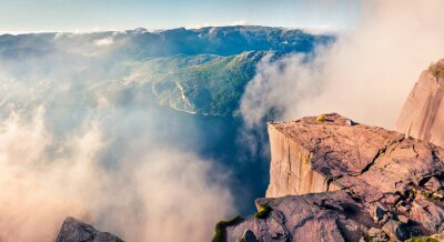 Fototapeta Foggy morning view of popular Norwegian attraction Preikestolen. Great summer scene of the Lysefjorden fjord, located in the Ryfylke area in southwestern Norway. Beauty of nature concept background.